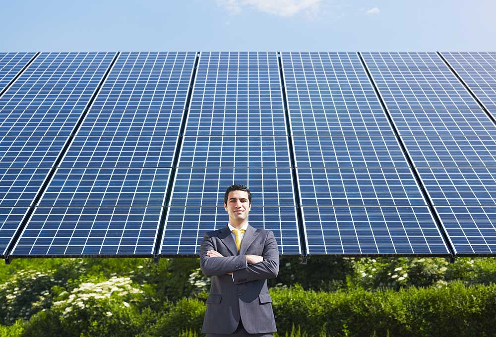 businessman in front of solar panels