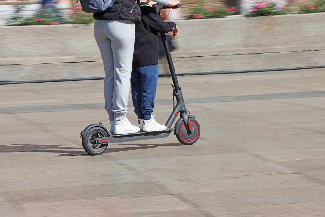 woman and son on electric scooter